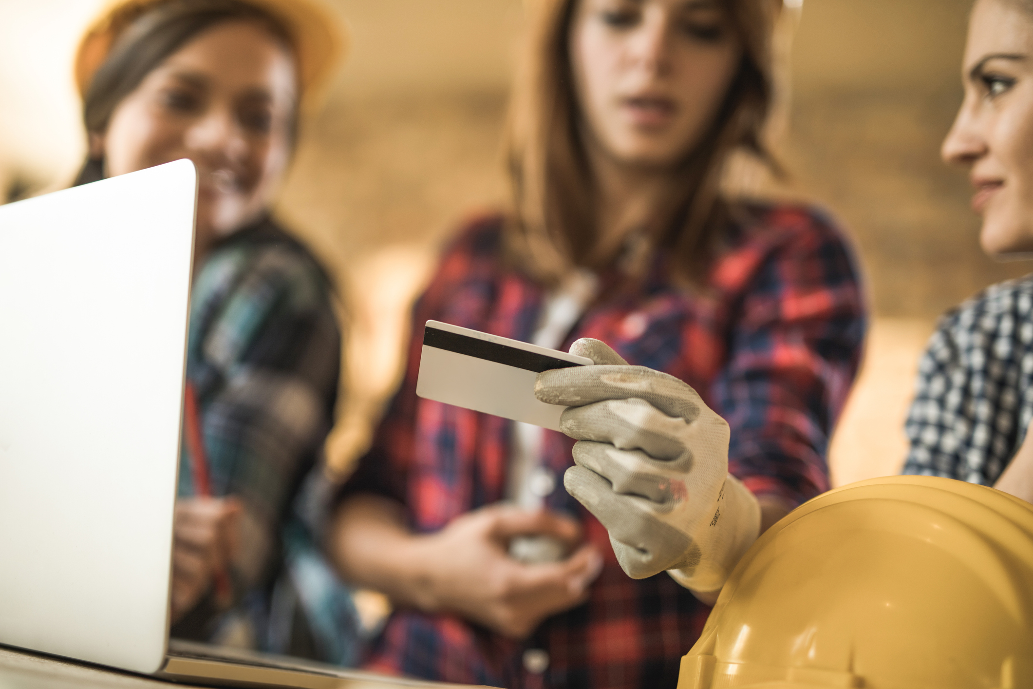 Trio of women in flannels and construction helmets looking at a credit card.