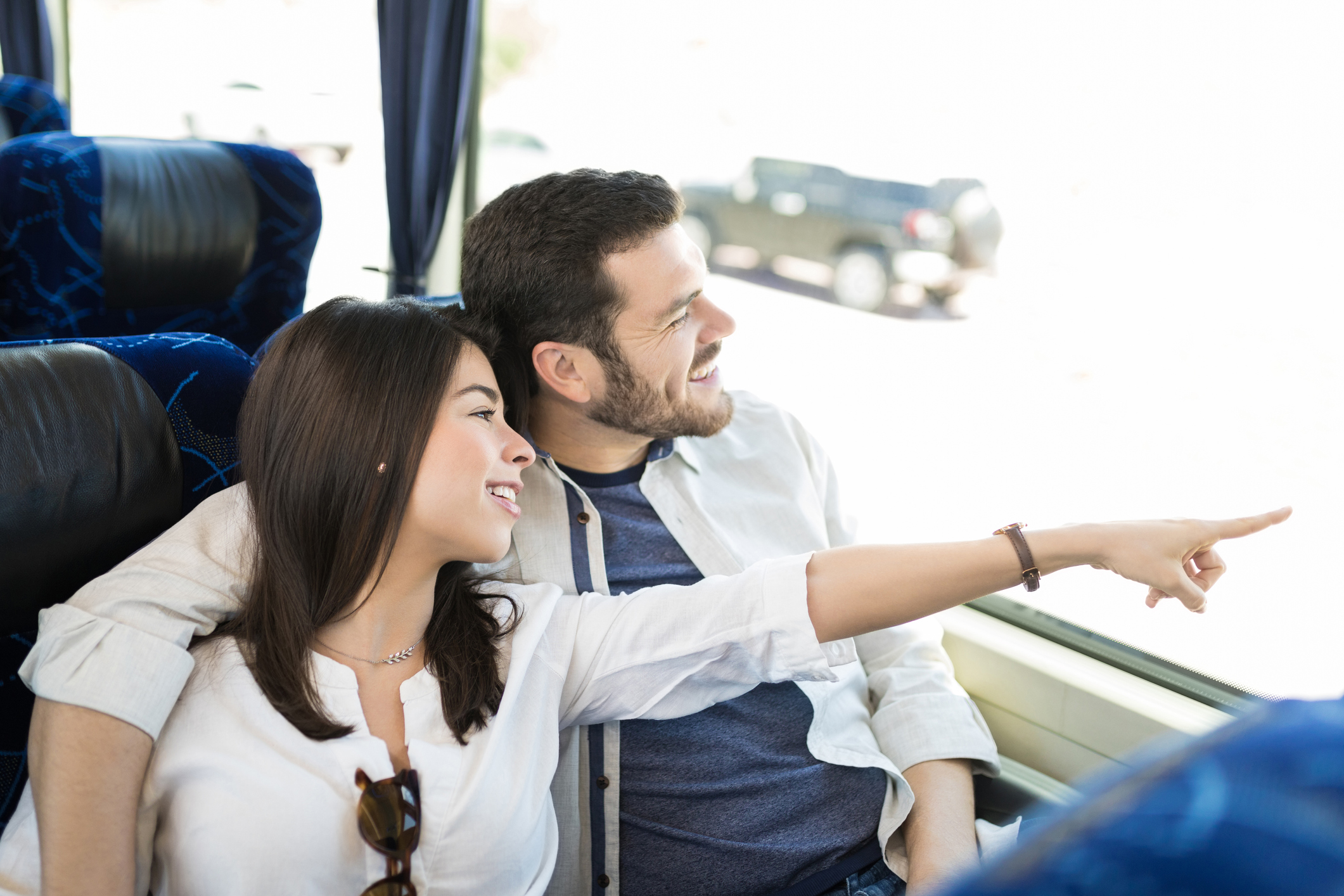Young couple on a bus smiling and looking at something through the window.