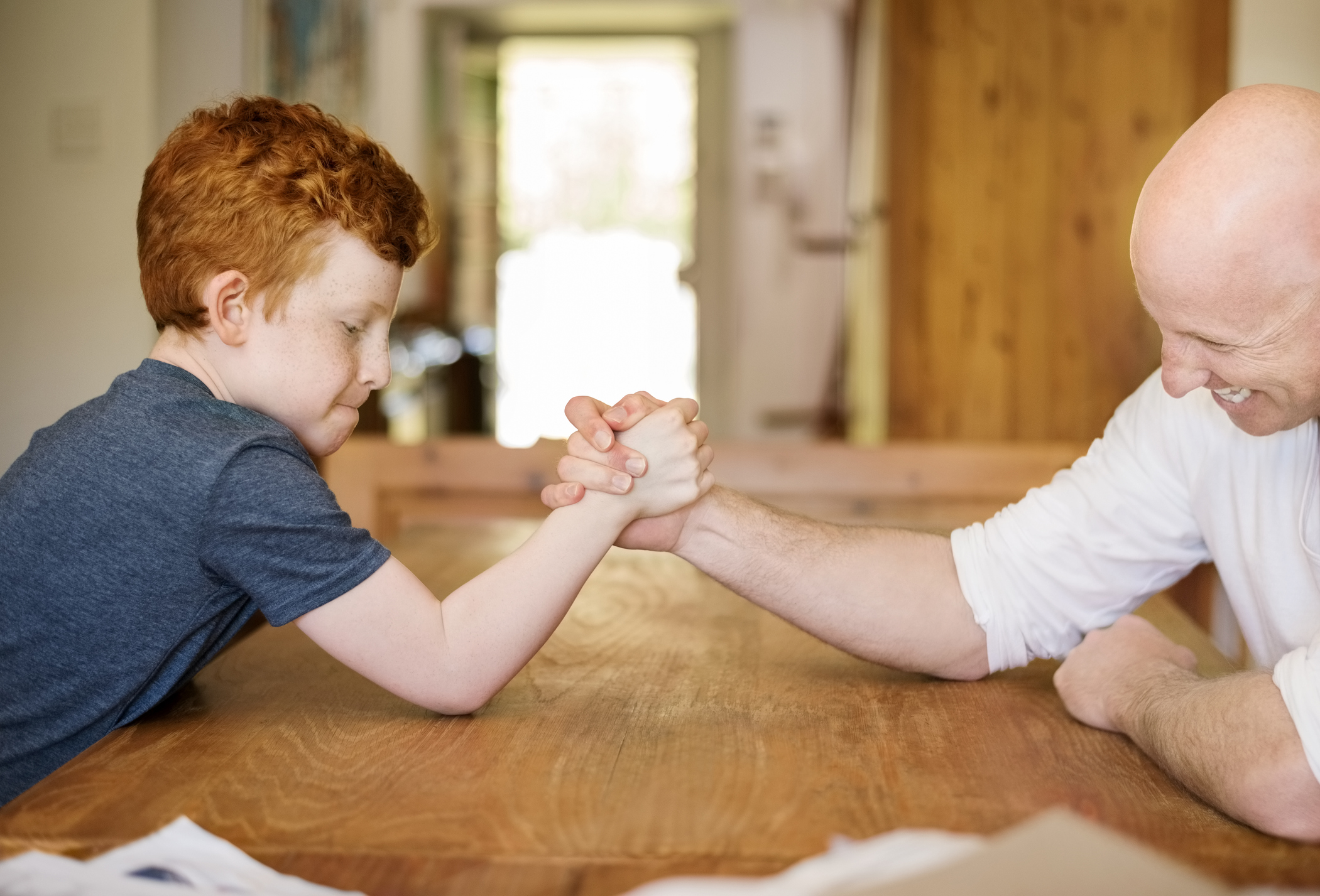Small child defeating grown man at arm wrestling.