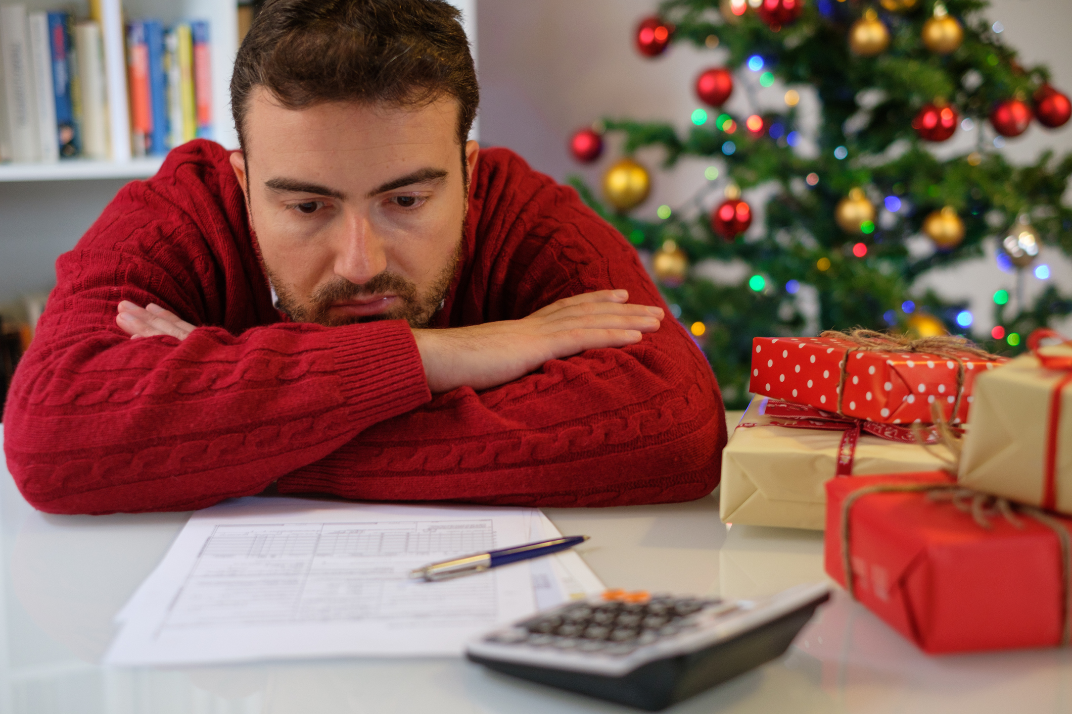 Man in festive sweater morosely slumped over desk looking at statements and calculator against Christmas tree backdrop.
